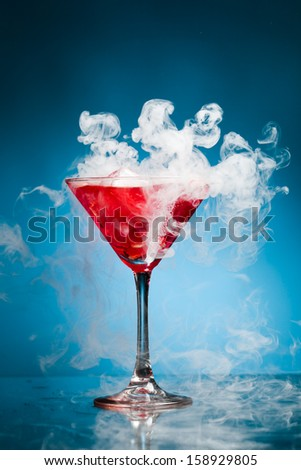 red cocktail with ice vapor, blue background - stock photo