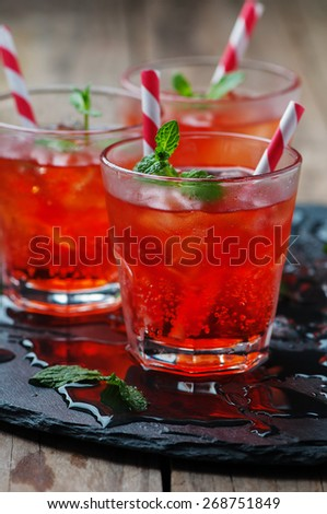 Red Cocktail with mint and ice, selective focus - stock photo