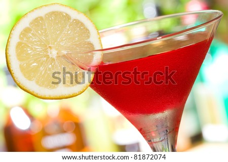 red cocktail with slice of lemon - stock photo