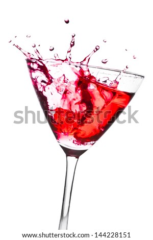 red cocktail with splashing in the tilted glass on a white background - stock photo