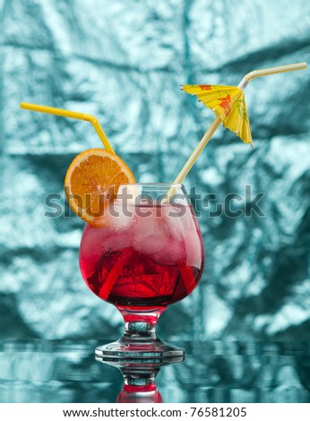 red coctail drink with ice cubs  on blue background. - stock photo