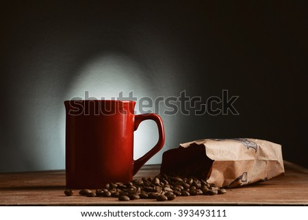 Red Coffee cup and saucer on a wooden table. Dark background. - stock photo