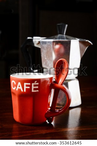 red coffee cup and  vintage coffeepot on dark wooden table - stock photo