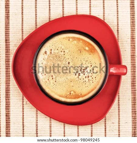 red coffee cup on striped tablecloth - stock photo