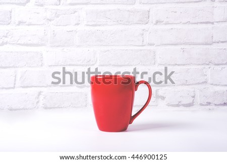 Red coffee cup on white table with white brick background  - stock photo