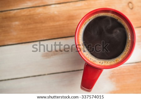 red coffee cup on wood table - stock photo
