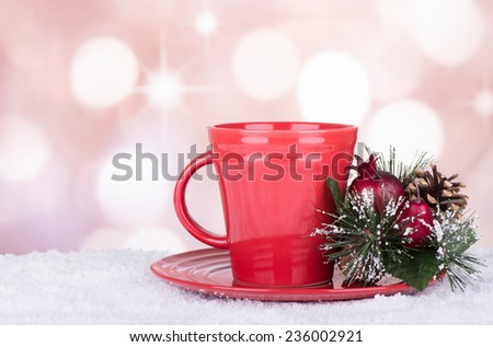 Red coffee cup with Christmas ornament on a bright colorful background - stock photo
