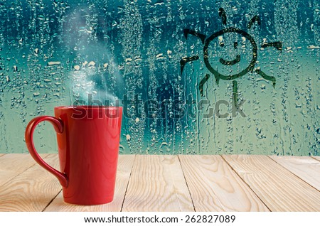 red coffee cup with smoke and sun sign on water drops glass window background - stock photo