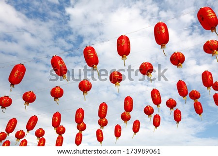 Red color Chinese Lunar New Year paper lantern hanging against a blue cloudy sky.  - stock photo