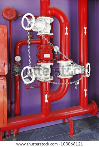 Red color fire fighting pipe system with an alarm bell hanging on a purple painted concrete wall.