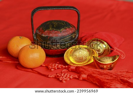 Red color, golden pineapples, mandarin oranges and gold ingots signifies prosperity / Auspicious ornaments / Chinese new year background - stock photo