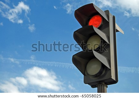 Red color on the traffic light with a beautiful blue sky in background - stock photo