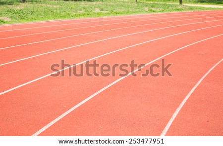 Red color running track in football stadium - stock photo