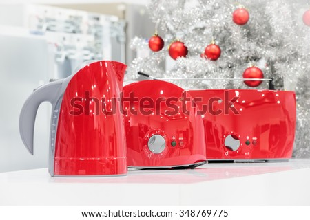 Red colored kettle and toasters in appliances store at Christmas - stock photo