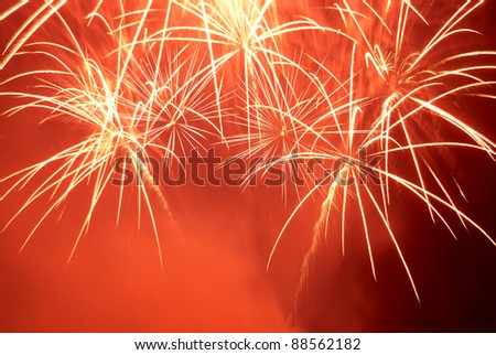 Red colorful fireworks on the black sky background. Holiday celebration. - stock photo