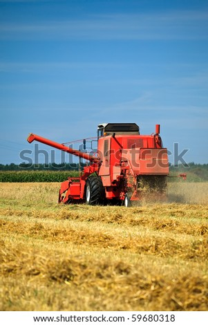 Red combine harvester working in a wheat field - stock photo