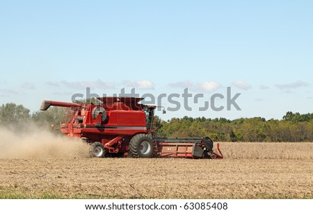 Red combine harvesting soybeans with a clear sky