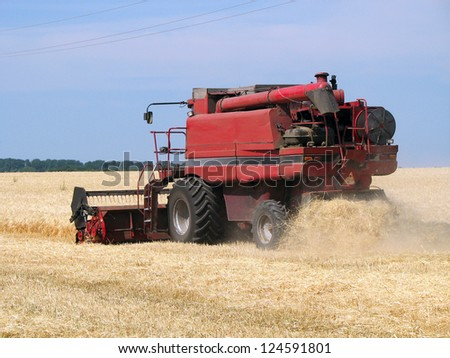 Red Combine on wheat field