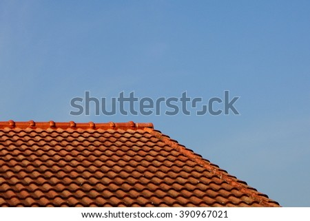 Red concrete roof against blue sky.