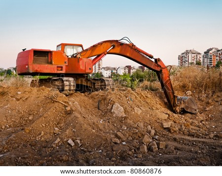 Red construction machine excavating earth near city - stock photo