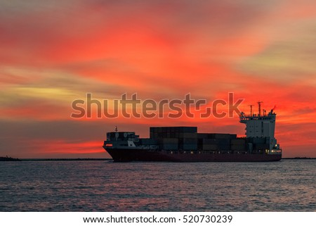 Red container ship arriving from Baltic sea at red sunset sky