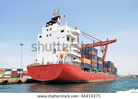 Red container ship at harbor - stock photo
