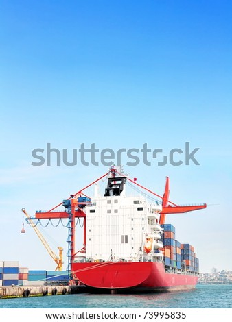 Red container ship under large blue sky - stock photo