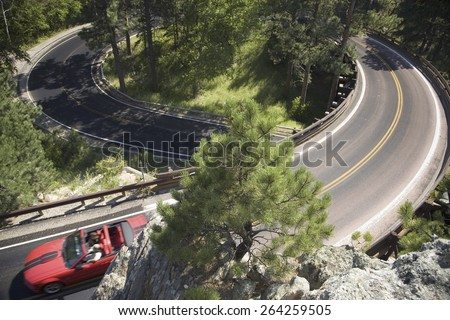 Red convertible driving on Iron Mountain Road, Black Hills, near Mount Rushmore National Memorial, South Dakota - stock photo