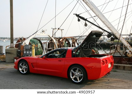 red corvette in front of boat harbor