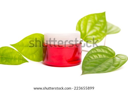 Red cosmetic bottle container with green leaves, isolated on white background. - stock photo