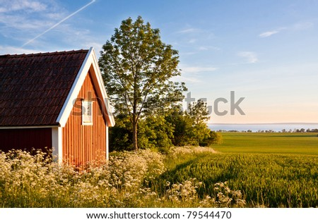 Red cottage at fields with a lake in the background. - stock photo
