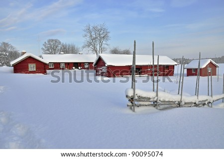 Red cottage in a wintry landscape - stock photo