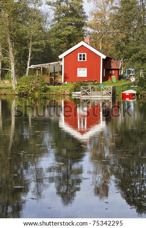 Red cottage with a jetty at the water - stock photo