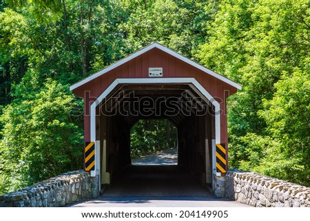 Red covered bridge during summer in Lancaster County Pennsylvania  - stock photo