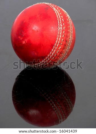 Red cricket ball on a black shiny surface - stock photo