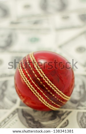 Red cricket on ball on money