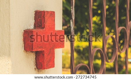 red cross on a fence. process color with vintage tone. - stock photo