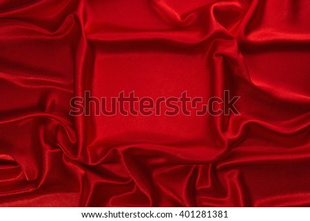 Red crumpled velvet with smooth rectangular plot as background.