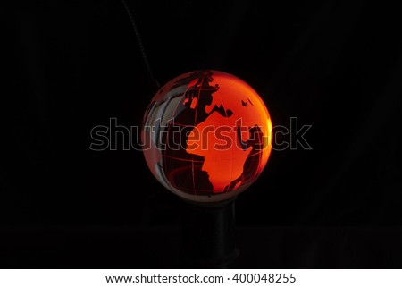 Red crystal globe, isolated on black background. - stock photo