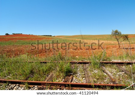 Red cultivated land and abandoned railroad - stock photo