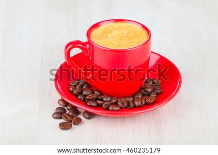 red cup coffee with coffee beans on wooden table  - stock photo