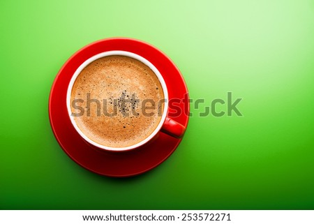 Red cup of coffee on green background - stock photo