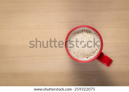 Red cup of coffee on wooden table - stock photo