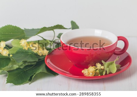 Red cup of linden tea  on white wooden background - stock photo