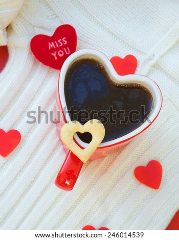 Red cup of tea in a form of heart. Shortcakes in the form of a heart close to the cup of tea. - stock photo