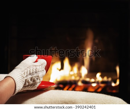 Red cup of tea or coffee in hands dressed in warm mittens near  fireplace. Winter and Christmas holiday concept - stock photo