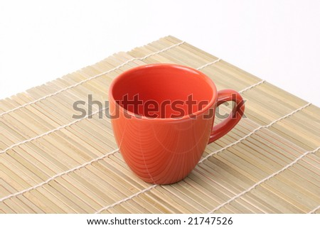 Red cup on bamboo corner isolated on white