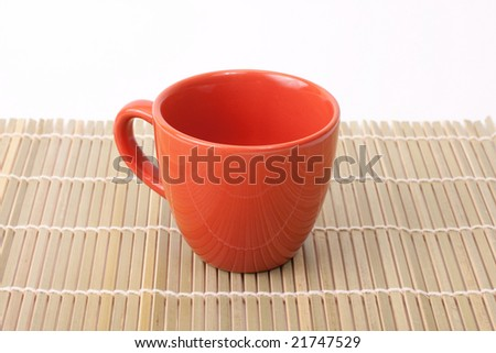 Red cup on bamboo isolated on white