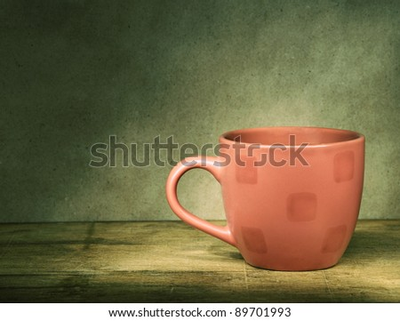 Red cup on the old wooden table.Selective sepia. - stock photo