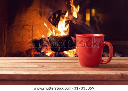 Red cup over fireplace on wooden table. Winter and Christmas holiday concept